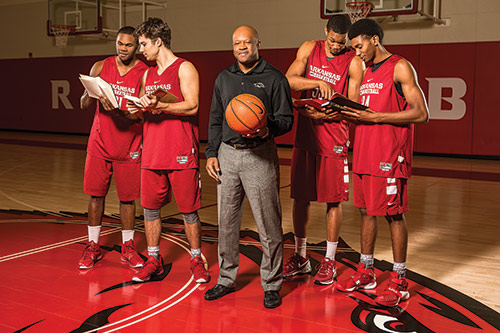 Coach Mike Anderson with Razorback basketball players holding books
